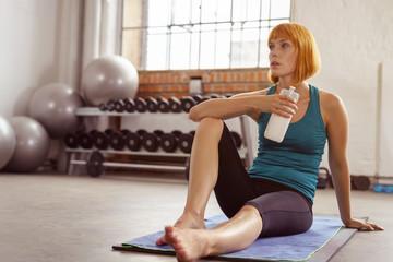 sportliche junge frau macht eine pause beim workout im studio