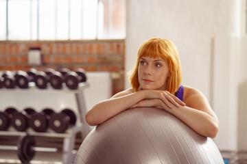 frau im fitnessstudio stützt sich auf gymnastikball