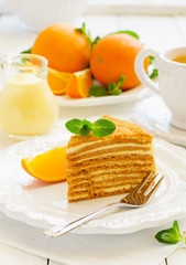 Homemade honey cake with orange cream on a white plate.