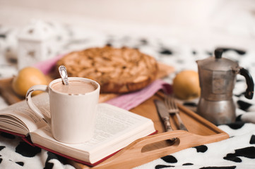 Cup of coffee staying on open book, apple pie on wooden tray closeup. Good morning. Selective focus.