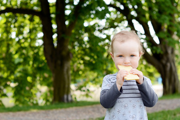 Little beautiful baby in the park eating peace of bread.