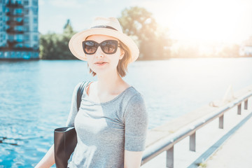 Serious woman with hat and sunglasses at river