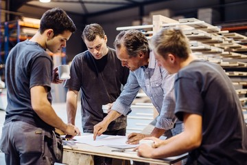 Male carpenter explaining blueprint to trainees in workshop