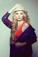 Young woman with camera. Blonde in a plaid shirt. Hipster fashio
