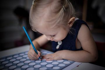 милая девочка склонилась над столом и рисует