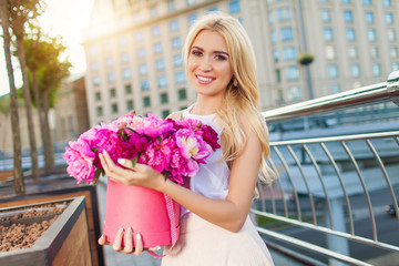 Portrait of young beautiful blonde woman with box of flowers posing in the city streets. flower box and gift box. bouquet of flowers in gift box. birthday, March 8, Valentine's Day, romantic