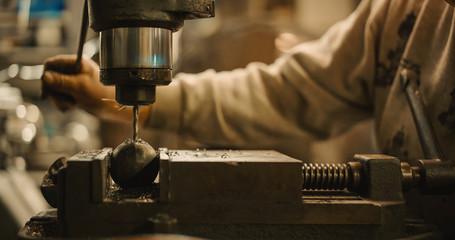 Craftsman operate a drill press.