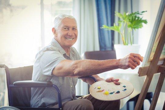 Happy senior man painting at home