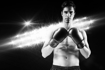 Composite image of portrait of boxer standing with boxing gloves