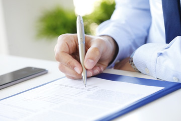 Signing the contract. Close-up image of a businessman's hands initialing some paperwork.