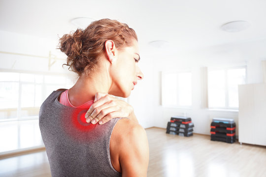 Sore after hard workout at fitness. Sporty woman putting her hand on red spot on while has sport injury in her shoulder.