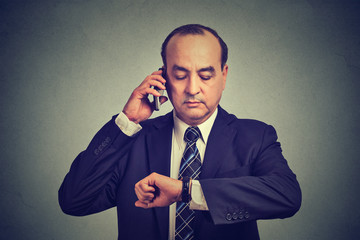 Business man looking at wrist watch, talking on mobile phone running late for meeting. Time is money