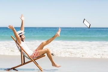Man throwing digital tablet on beach