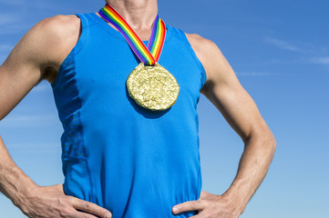 Gay athlete standing with gold medal and rainbow ribbon against blue sky close-up