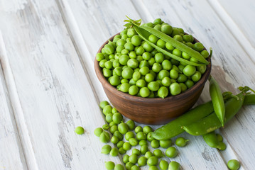 Green peas in a ceramic bowl and pods of peas on a wooden table