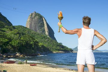 Young athletic man standing with sport torch against Rio de Janeiro Brazil skyline at Praia Vermelha Red Beach with Sugarloaf Mountain
