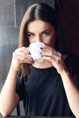 Young beautiful girl drinking tea in cafe, holding cup both hands and thoughtfully looking at camera. Girl enjoying her leisure time alone in coffee shop cafe. Girl with green eyes in black t-shirt.