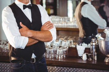 Mid section of bartender standing with arms crossed