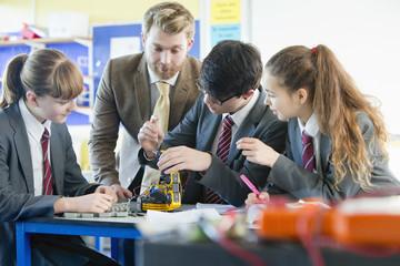Teacher guiding high school students assembling robot in science class
