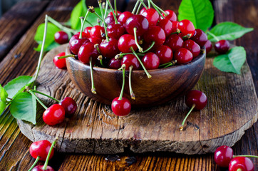 Fresh cherry in a wooden bowl on a wooden table