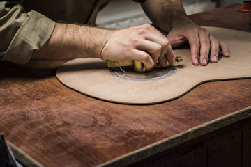 Luthier manufacturing a guitar in his workshop, close-up
