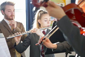 Teacher teaching high school students playing flute and violin in music class