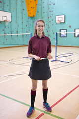 Portrait smiling high school student holding badminton racket in school gymnasium