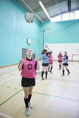 High school student catching netball in gym class