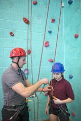 Gym teacher preparing rock climbing safety equipment for high school student
