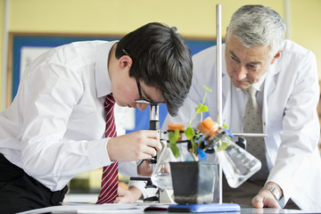 Teacher helping high school student using microscope in biology class