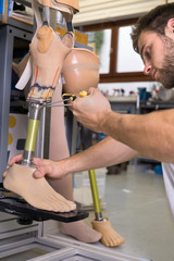 Close up of man adjusting false limb.