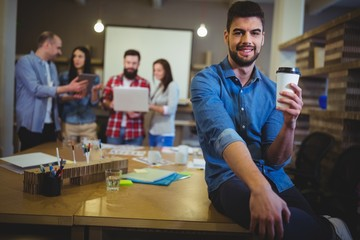 Young businessman holding disposable cup while sitting on table