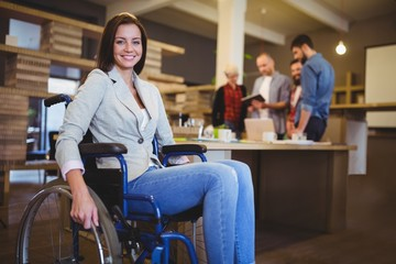 Confident disabled businesswoman by desk