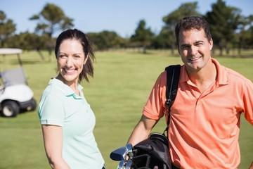 Portrait of confident golfer couple