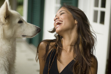 Woman laughing next to dog