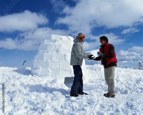 Two people carrying ice block and building igloo for Ice block construction