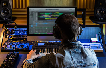 One man produce electronic music in project home studio.