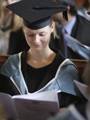 Young woman wearing graduation cap and gown indoors