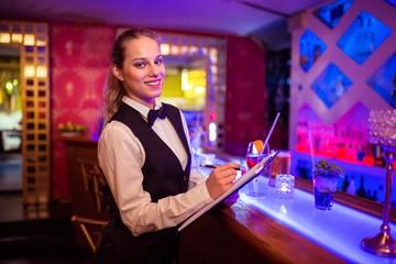 Barmaid writing in clipboard at illuminated bar counter