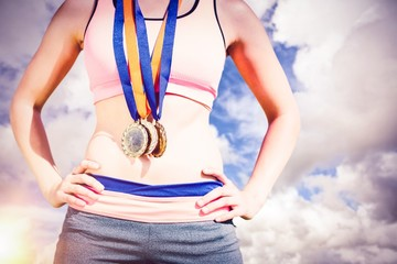 Composite image of portrait of sporty woman chest holding medals