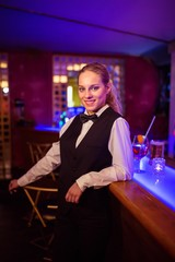 Beautiful bartender leaning at bar counter