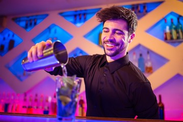 Barkeeper pouring cocktail in glass