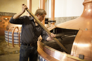 Brewer measuring the volume of mash at brewery in Traunstein, Bavaria, Germany
