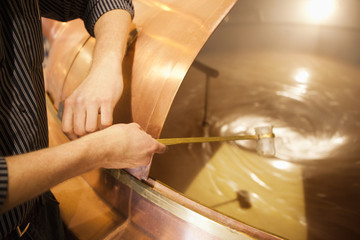 Brewer taking mash sample at brewery in Traunstein, Bavaria, Germany