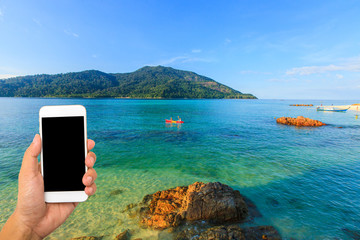 Hand hold smartphone on beautiful tropical beach and sea background