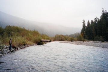 man standing by river, olympic national park, washington,