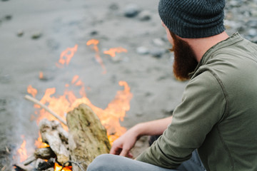 Over the shoulder view of bearded man by campfire