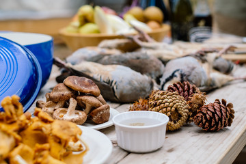 Game birds and mushrooms on wooden table