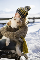 Woman embracing pet dog in snow