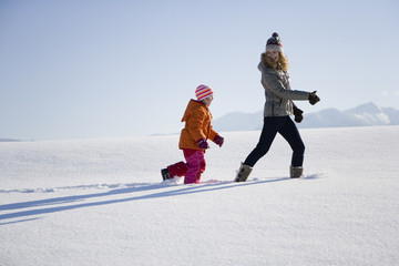 Mother and daughter walking in snow